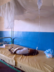 Matimu at the public hospital in Tamatave, shortly after checking in. A bare bed and the I/V is tied to the bed post with another I/V tube.