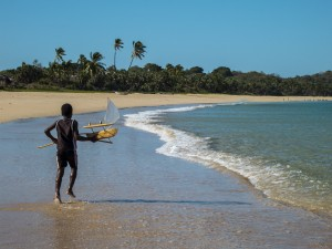 A boy on Nosy Mitsio taking advantage of the northeast winds to launch his homemade canoe out into the ocean!