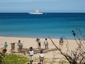 A huge yacht and train of smaller ships sailing by the beach of Nosy Mitsio.